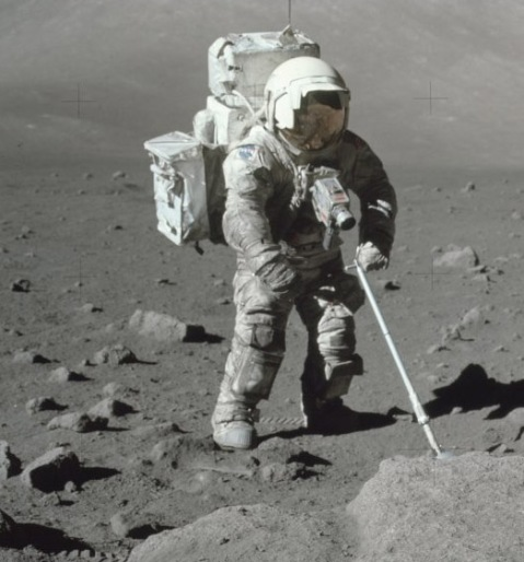 Colour photograph of Jack Schmitt with his spacesuit covered in moondust.